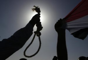 An Egyptian anti-Mubarak protester holds a noose during a protest outside the police academy in Cairo, Egypt, Wednesday, Aug. 3, 2011, where ousted President Hosni Mubarak, his two sons Alaa and Gamal, his security chief Habib el-Adly and six top police officers face trial, on charges they ordered the use of lethal force against protesters during Egypt's 18-day uprising. Some 850 protesters were killed. Egyptian flag is seen at right.  (AP Photo/Amr Nabil)
