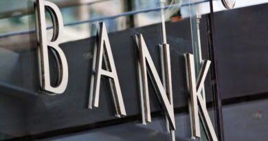 Modern metal Bank sign lettering fixed to a glass wall, with reflections in the glass.