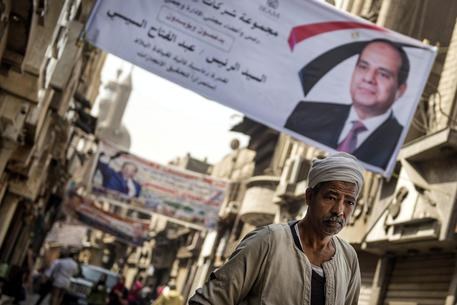epa06620179 A man walks underneath electoral posters for President Abdel Fattah al-Sisi, at Muizz street, Cairo's oldest street, Egypt, 22 March 2018. Egyptian Presidential election will be held between 26 and 28 March 2018. Moussa Mostafa Moussa, the head of el-Ghad party is running against Incumbent President Abdel Fattah al-Sisi.  EPA/MOHAMED HOSSAM