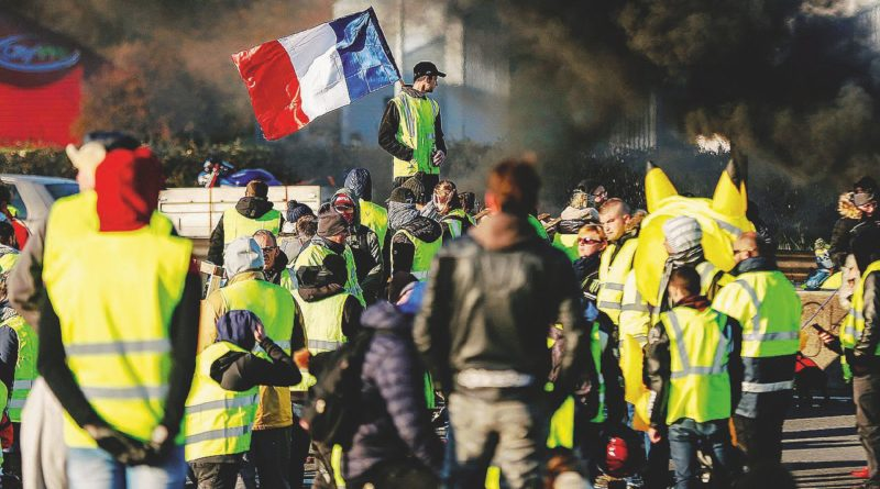 "TOPSHOT - People block Caen's circular road on November 18, 2018 in Caen, Normandy, on a second day of action, a day after a nationwide popular initiated day of protest called ""yellow vest"" (Gilets Jaunes in French) movement to protest against high fuel prices which has mushroomed into a widespread protest against stagnant spending power under French President. (Photo by CHARLY TRIBALLEAU / AFP)"