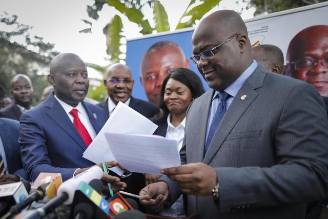 epa07185144 DR Congo's opposition leader Felix Tshisekedi (R), the leader of the Union for Democracy and Social Progress (UDPS) party, exchanges documents with Vital Kamerhe (L), the leader of the Union for the Congolese Nation (UNC), during a news conference to announce the opposition coalition's presidential candidate in Nairobi, Kenya, 23 November 2018. Opposition leaders have chosen Tshisekedi to take on Emmanuel Ramazani Shadary who is backed by President Joseph Kabila in the December 2018 elections.  EPA/DAI KUROKAWA