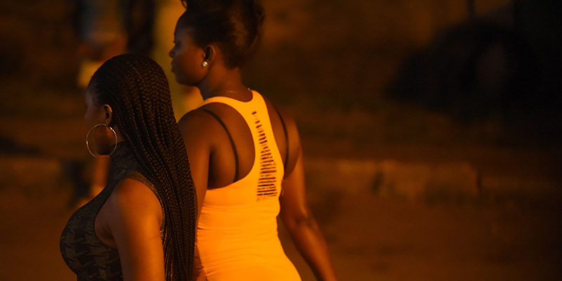 "Prostitutes stand walk on the street in Benin City, capital of Edo State, southern Nigeria, on March 29, 2017.  In Benin City, Nigeria's capital of illegal migration, no one says the word ""prostitution"". The word on the street for the young girls who leave for Italy or France is ""hustling"". About 37,500 Nigerians arrived in Italy by boat in 2016, more than from any other African country, and most of them were from the southern city, the capital of Edo state.   / AFP PHOTO / PIUS UTOMI EKPEI        (Photo credit should read PIUS UTOMI EKPEI/AFP/Getty Images)"