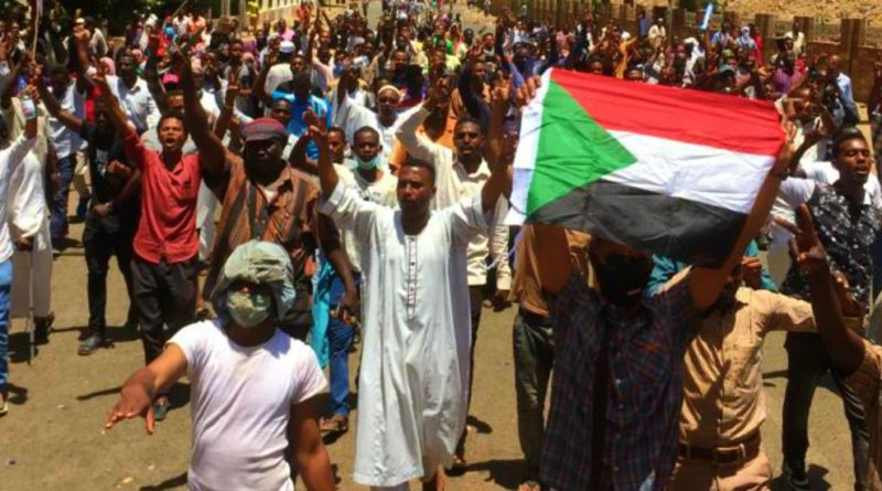 Sudanese protesters raise a national flag and chant slogans as they rally in front of the military headquarters in the capital Khartoum on April 8, 2019. - Sudan's army deployed around its Khartoum headquarters Monday as thousands of protesters urging the military to join calls for leader Omar al-Bashir's resignation defied tear gas to demonstrate for a third day, witnesses said. (Photo by STRINGER / AFP)