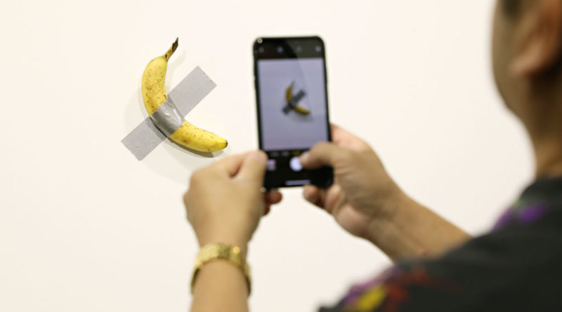 """MIAMI BEACH, FL - DECEMBER 06:  People post in front of Maurizio Cattelan's """"Comedian"""" presented by Perrotin Gallery and on view at Art Basel Miami 2019 at Miami Beach Convention Center on December 6, 2019 in Miami Beach, Florida. Two of the three editions of the piece, which feature a banana duct-taped to a wall, have reportedly sold for $120,000.  (Photo by Cindy Ord/Getty Images)"""